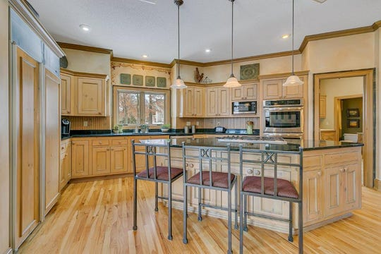 The gourmet kitchen features a gas cooktop island with plenty of seating.