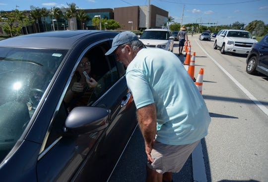 David Gladding (right) of Martin County Parks and Recreation, checks the residency of a beach-bound driver on Tuesday, May 12, 2020, at the entrance to Stuart Beach on Hutchinson Island in Martin County. Martin County opened its beaches on Mother's Day weekend, but is limiting access for Martin County residents only as COVID-19 restrictions are eased.