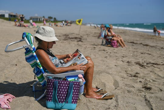 "Susan Buckman, of Hobe Sound, enjoys a day at Stuart Beach on Tuesday, May 12, 2020, on Hutchinson Island in Martin County. ""I think people need to get out and have fresh air, vitamin D, walk, read, swim, and enjoy life,"" Buckman said. Martin County opened its beaches on Mother's Day weekend, but is limiting access for Martin County residents only as COVID-19 restrictions are eased."