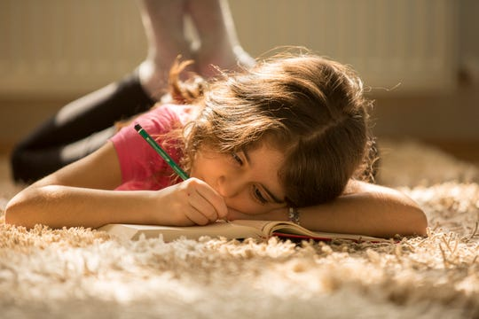 A young girl lies on the floor while writing a story.
