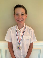 Trent Walz of St. Mary School in Vineland shows of the medal he received for being a finalist in the Partnership for a Drug-Free New Jersey's Design a Fourth Grade Folder contest.