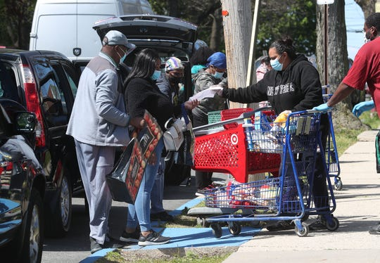 Residents unload shopping carts full of food that were given out at the food pantry program at the Martin Luther King Multipurpose Center in Spring Valley May 12, 2020.