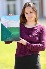 Rita Hoffmeister, a member of Pleasantville High School's Class of 2020, as photographed by Chad Kraus outside the school. Hoffmeister poses with an acrylic painting  -- an art class project that is unfinished.