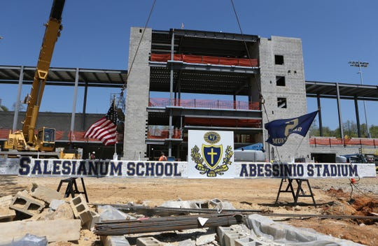 The final beam - signed by members of the Salesianum community - is ready to be lifted into place at Abessinio Stadium in a ceremonial topping off at the former Baynard Stadium Wednesday.