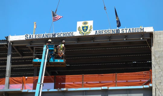 The final beam - signed by members of the Salesianum community - is lifted into place at Abessinio Stadium in a ceremonial topping off at the former Baynard Stadium Wednesday.