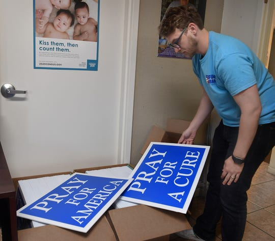 Simon Welch, marketing director for the Wichita Falls Area Food Bank, shows the signs that are available to help garner donations for the food bank. The signs are available for donations of any amount.