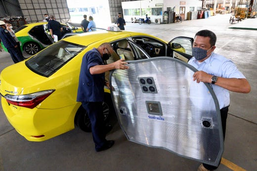 A taxi driver and a mechanic install a bulkhead barrier against the spread of COVID-19 novel coronavirus, made by Thai military aeronautical engineers, in Bangkok on May 13, 2020.