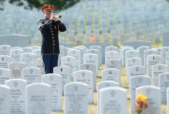In this file photo from 2013, a bugler plays Taps during the burial service at Arlington National Cemetery in Arlington, Virginia, for Army Air Force 2nd Lt. Valorie L. Pollard and Army Air Force Sgt. Dominick J. Licari, who went missing during World War II. Such traditional military funeral ceremonies are largely on hold due to the coronavirus pandemic. Veterans affairs officials say that as soon as it is safe, the playing of taps and rifle salutes will be done for those veterans who have passed away during this time of social distancing.