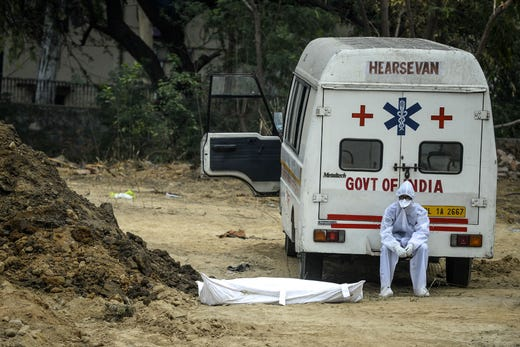 A health worker wearing protective gear sits on an ambulance next to the dead body of a victim who died from the COVID-19 coronavirus before the burial at a graveyard in New Delhi on May 13, 2020.