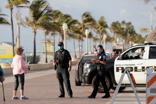 Hollywood police officers monitor activity along the Hollywood Beach Broadwalk during the new coronavirus pandemic, Wednesday, May 13, 2020, in Hollywood, Fla.