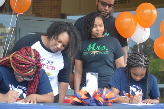 Pineville senior powerlifters Brionna Ford (bottom left) and Xacaria Clark (bottom right) signed with Midland University (Neb.) Wednesday.