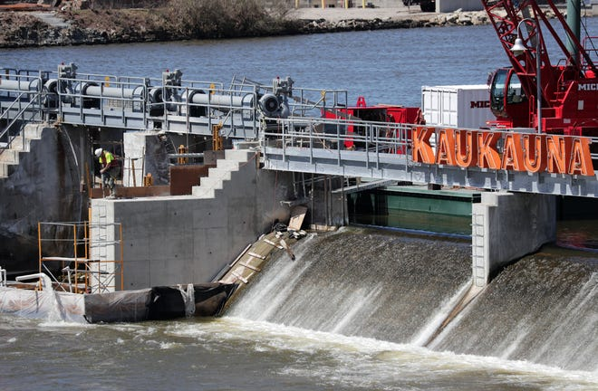 Employees of Michels Corp. repair the Tainter gates at the Kaukauna dam. The $3.5 million project is being funded by the U.S. Army Corps of Engineers.
