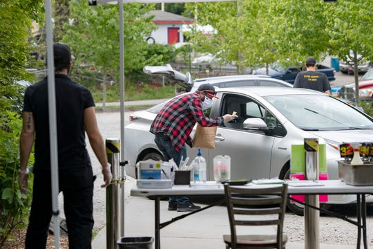 Eric Roberts delivers an order to a car as he works the take-out tent at Rocky's Hot Chicken Shack on Sweeten Creek Road on May 13, 2020. Restaurants in North Carolina are currently only allowed to sell food to go.
