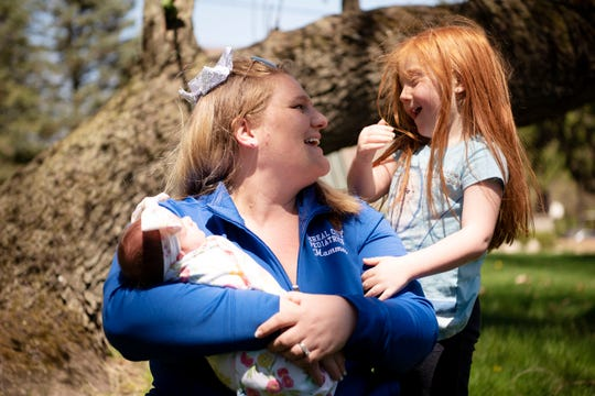 Katheran Hammer poses for a portrait with her daughter Kaley, 5, and newborn Kori on Wednesday, May 6, 2020 in their yard in Battle Creek, Mich. Kori was born during the COVID-19 pandemic on April 23, 2020.