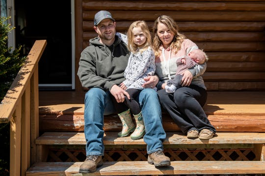 Jason and Hallie DiBartolomeo pose for portrait with their children Stella, 4, and newborn Nico on May 4, 2020 on their porch in Battle Creek, Mich. Nico was born during the COVID-19 pandemic on March 19, 2020.