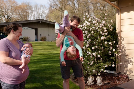 Mike Horton picks up his daughter Saige, 3, as his wife Shannon Horton holds their newborn son Tate on Thursday, May 7, 2020 at their home Battle Creek, Mich. Tate was born during the COVID-19 pandemic on April 9, 2020.