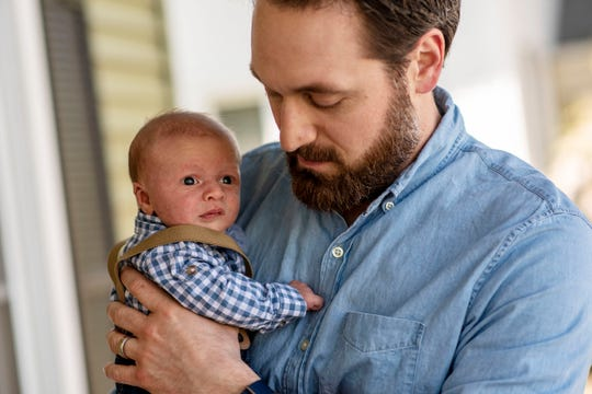 Phil Voss holds his son Ethan on Wednesday, May 6, 2020 at their home in Marshall, Mich. Ethan was born during the COVID-19 pandemic on April 5, 2020.