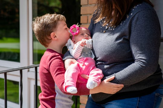Chelsea Dow holds newborn Aria for her son Aiden Dow, 5, to kiss on Monday, May 4, 2020 on their porch in Battle Creek, Mich. Aria was born during the COVID-19 pandemic on March 25, 2020.
