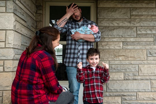 Brooke and Tyler Hutcheson pose for a portrait with their children Wyatt, 4, and newborn Rose on April 9, 2020 on their porch in Battle Creek, Mich. Rose was born during the COVID-19 pandemic on March 24, 2020.