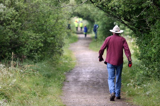 Tex Lewis wears his trademark hat as he walks on the Clear Creek Trail in Silverdale in 2013.