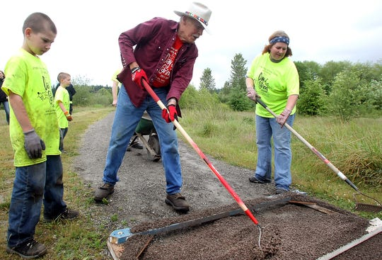Tex Lewis shows Day of Caring volunteers Davy Young, 8, left, and his mom Sarah Young how to spread the crushed trail rock on the Clear Creek Trail in Silverdale in the 2013 file photo.
