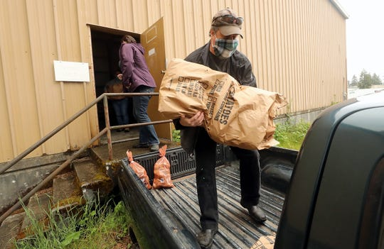 Kitsap Harvest's Brian Dickerson loads sacks of potatoes into the back of Myra Battin's truck at Peninsula Truck Lines in Bremerton on Thursday. Kitsap food banks teamed up to transport the spuds from eastern Washington to benefit Kitsap residents in need of food assistance.