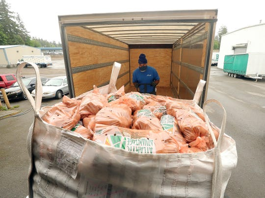Mike Smith, an employee of Hill Moving Services, loads up a truck with potatoes at Peninsula Truck Lines in Bremerton on Thursday. Hill Moving Services donated its time and a truck to help get the potatoes to the food banks from the drop-off point at Peninsula Truck Lines.