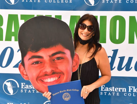 Proud mom Jesse DeLeon holds up a giant cut out of her son Rolando Gomez, who couldn't make it to the Thursday morning graduation event at EFSC to pick up his diploma cover.