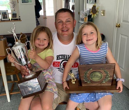 Champlain Valley baseball coach Tim Albertson, center, and  daughters Juliette, left, and Hadley pose with the Redhawks' 2019 championship trophies.