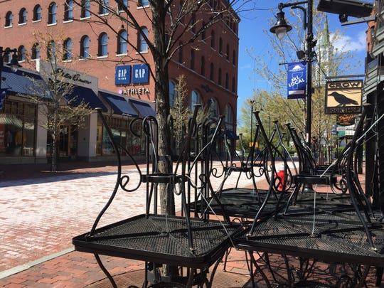Outdoor-cafe tables are stacked outside Halvorson's Upstreet Cafe on a desolate Church Street Marketplace on May 13, 2020.