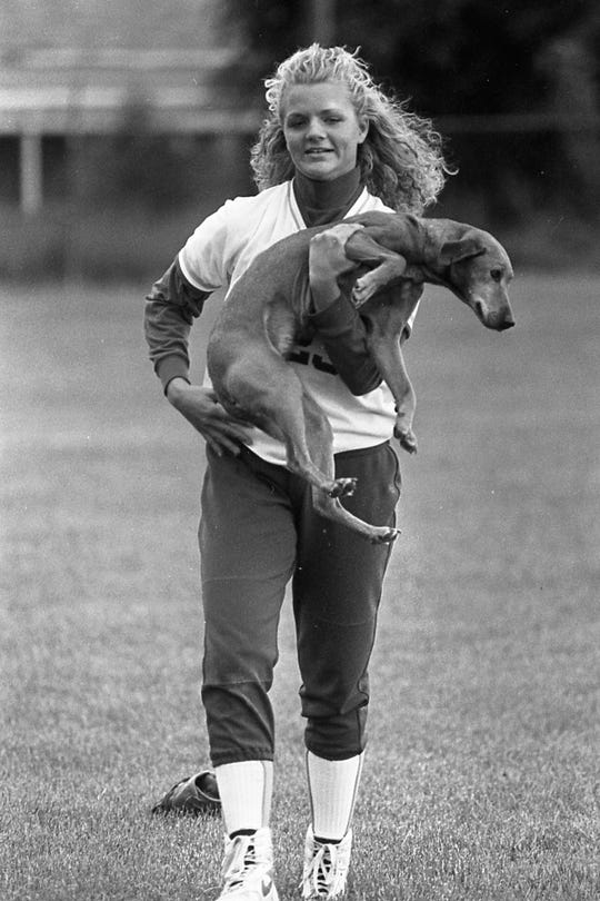 Lucasville Valley shortstop Andrea Smalley carries a dog off a field during a game. Piketon fell to Lucasville Valley in the 1994 district final. It was a game marked by a dog running onto the field.