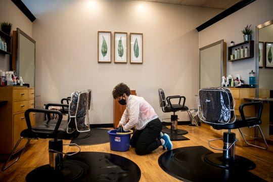 Karen Geiger, owner of Anthony's Salon in Green Township, sanitizes her salon on Thursday, May 14, 2020. After being shut down for weeks to battle the pandemic, Anthony's will open at 9 a.m. on Friday with extended hours and strict new rules.