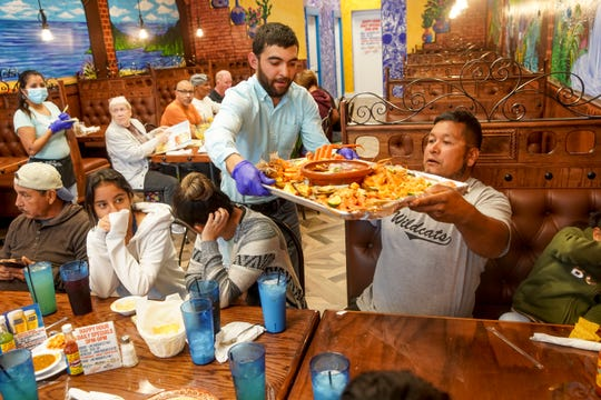 Martin Melendez presents the Charola Costa Azul to the Narajo family at Costa Azul Grill & Bar in Clarksville, Tenn., on Wednesday, May 13, 2020.