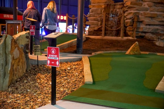 Signs at each hole advise customers to practice social distancing in mini golf at The City Forum in Clarksville, Tenn., on Wednesday, May 13, 2020.