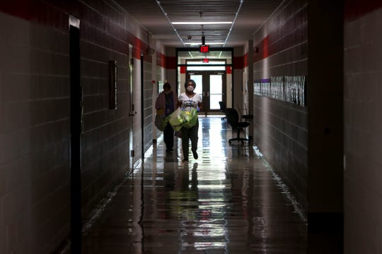 Amelia Cooper, right, a pre-K assistant, walks down the hall with Mary Jo Schmidt, a special education pre-K assistant as they carry bags with students belongings and school work down the hall at Minglewood Elementary School in Clarksville, Tenn., on Thursday, May 14, 2020.