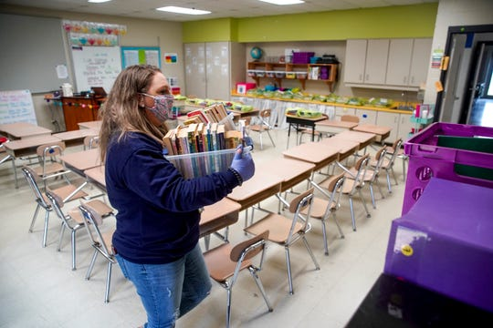 Katie Worsham, a fourth grade teacher, walks containers filled with books back to a corner of her classroom preparing to take them home and pack up her student's belongings at Minglewood Elementary School in Clarksville, Tenn., on Thursday, May 14, 2020.