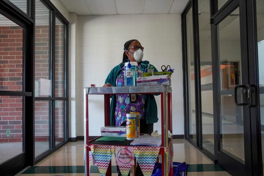 Sandra Rice, the school nurse, stands at her station in the front foyer ready to take temperatures and screen employees arriving to clean out classrooms at Minglewood Elementary School in Clarksville, Tenn., on Thursday, May 14, 2020.