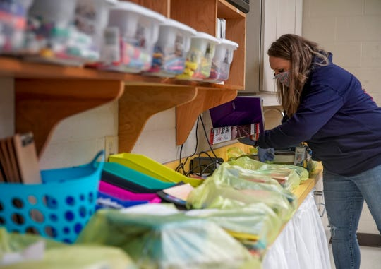Fourth grade teacher Katie Worsham places students belongings and school supplies into bags that will be let out for them to pick up in the front lobby at Minglewood Elementary School in Clarksville, Tenn., on Thursday, May 14, 2020.