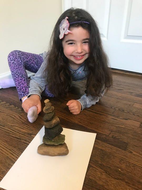 Sydney Collman displays a rock carin that she created in the DIY club.