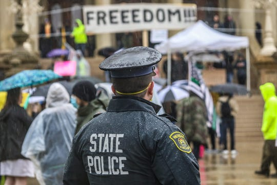 Michigan State Police look on during the a protest rally against Gov. Gretchen Whitmer's order to stay home during COVID-19 pandemic in Lansing, Mich. on Thursday, May 14, 2020.
