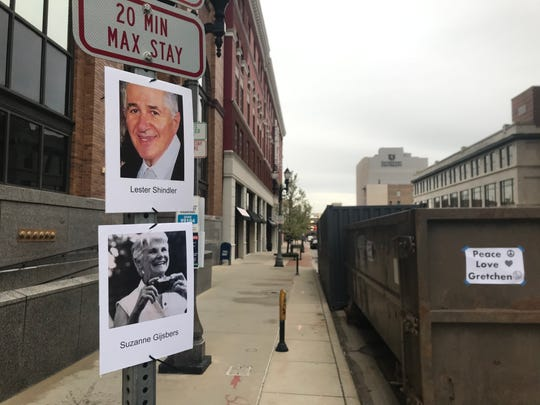 Portraits of individuals who died with COVID-19 hang near the Michigan Capitol on Thursday, May 14, 2020, ahead of a protest against restrictions that aim to stem the spread of the virus.