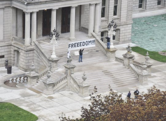 Protesters in Lansing get an early start on Thursday, May 14, 2020, demonstrations by hanging a sign above the Capitol stairs.