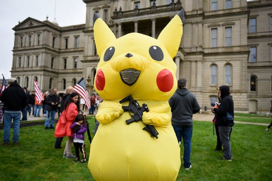 A large Pikachu holds an AR-9 assault-style gun during a protest at the state Capitol to oppose the executive orders Gov. Gretchen Whitmer issued in response to the coronavirus pandemic, Thursday, May 14, 2020.