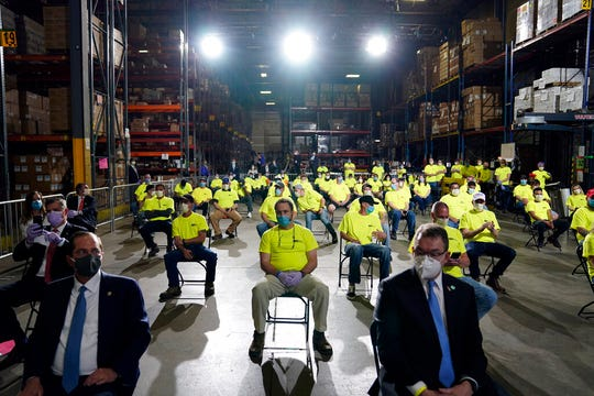 People listen as President Donald Trump speaks after a tour of Owens & Minor Inc., a medical supply company, Thursday, May 14, 2020, in Allentown, Pa.