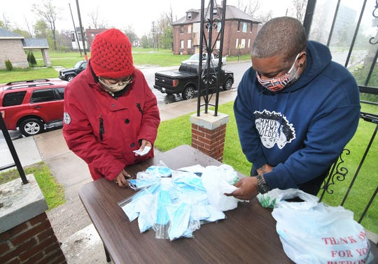 Sandra Lyght of Detroit gets face masks and hand sanitizer from Yusef Shakur, Michigan Roundtable co-director, at the Community Movement Builders center in Detroit.