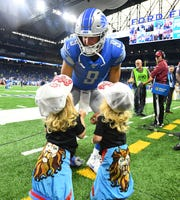Lions quarterback Matthew Stafford visits with his daughters, twins Sawyer and Chandler, before a game last season.