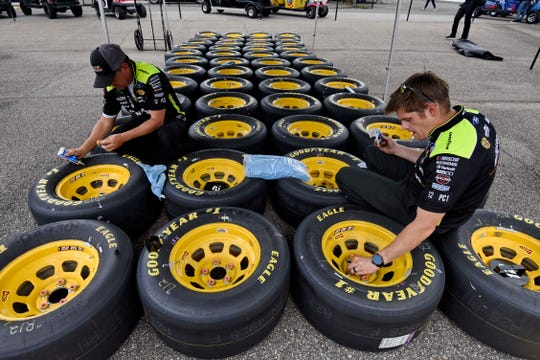 Crew members prepare tires before the NASCAR Cup Series auto race at Darlington Raceway in September.