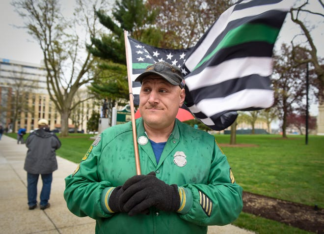 Warren city councilman Eddie Kabacinski holds a flag during a protest at the state Capitol to oppose the executive orders Gov. Gretchen Whitmer issued in response to the coronavirus pandemic, Thursday, May 14, 2020.