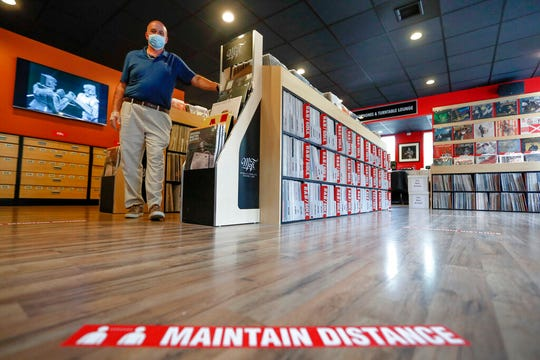 """Mark Mawhinney walks past one of the racks of records towards the sticker on the floor reminding customers to maintain distances in his """"Music to My Ears"""" retail record and HiFi store, Thursday, May 14, 2020, in Pittsburgh. He was preparing the store to re-open Friday when some of the COVID-19 restrictions will be lessened in Pittsburgh and several western Pennsylvania counties as they move from red to yellow status."""