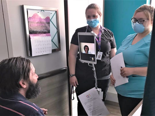 Kevin Hartman, left, a resident at the Corning Center for Rehabilitation and Healthcare, meets virtually with nurse practitioner Joy Obihara of New York City. Looking on are Corning Center telemedicine clinical technicians Deanna Wheeler, right, and Gwen Youmans.